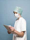 Nurse with surgical mask and a journal poster