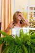 Frau gießt ihre Blumen in der Wohnung