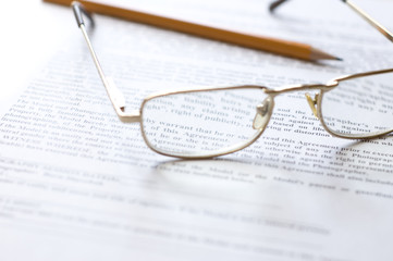 Close-up of document, eyeglasses and pencil.
