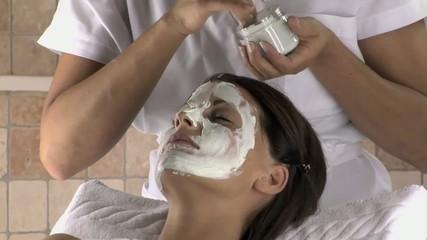 mano di estetista mette crema sul viso