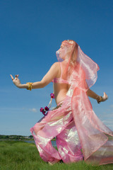 a woman in pink dancing on the grass