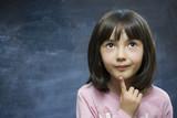Adorable schoolgirl stay near school blackboard. poster