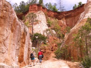 Hikers walking at the bottom of a dirt canyon