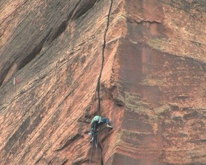 Rock Climber on a 200 foot rock face in Zion National Park Utah