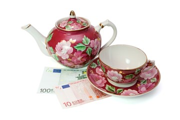 Tea service stands on euro banknotes isolated