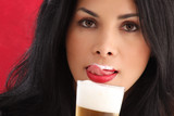 Cute brunette drinking beer and liking foam from her lips poster