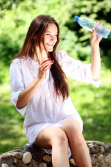 young woman pours over herself water from a bottle