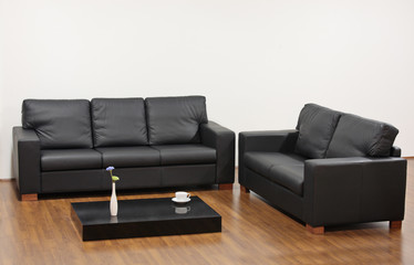 A modern minimalist living room with black furniture