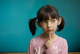 Pensive schoolgirl stay near school blackboard. poster