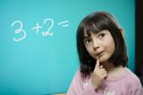 Funny schoolgirl stay near school blackboard. poster