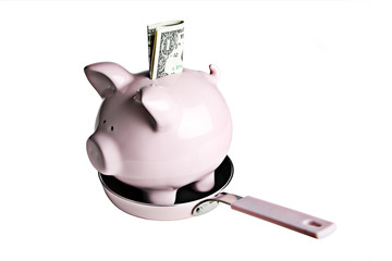 Pink piggy bank and dollar bills in a pink frying pan