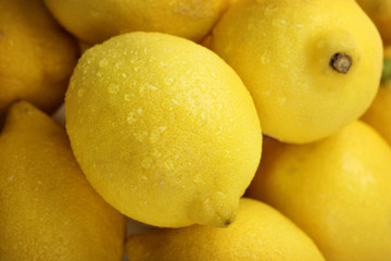 closeup of a pile of fresh lemons with water drops
