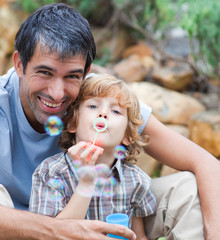 Portrait of a father and son blowing bubbles