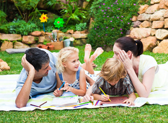 Happy family drawing in a park