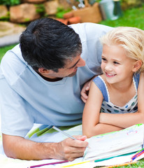 Dad and daughter doing homework in a garden