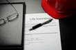 Life insurance concept: document form, pen and red helmet