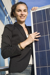 Young woman holding a solar panel