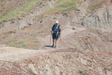 Backpacker hikes on a desert path poster