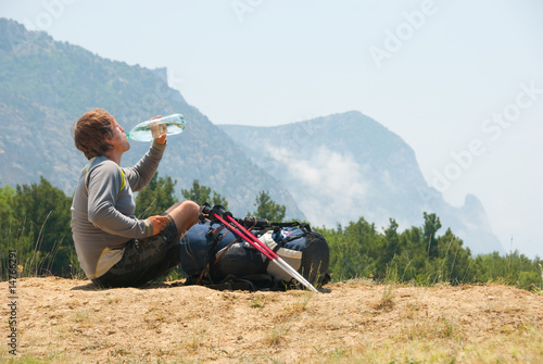Tired hiker drinks water