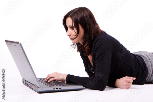 lying woman writting on laptop