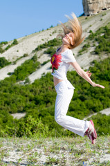an emotional woman is jumping at the mountains