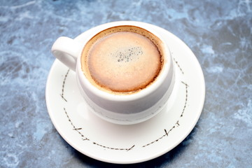 A cup of coffee on the blue table