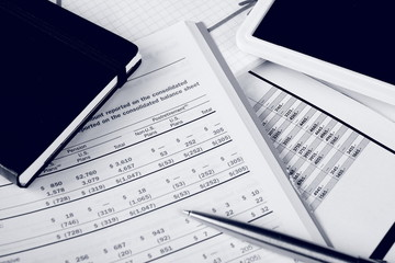 Monochrome daily financial reports, pen and notepad