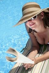 Mujer Leyendo al lado de una Piscina azul