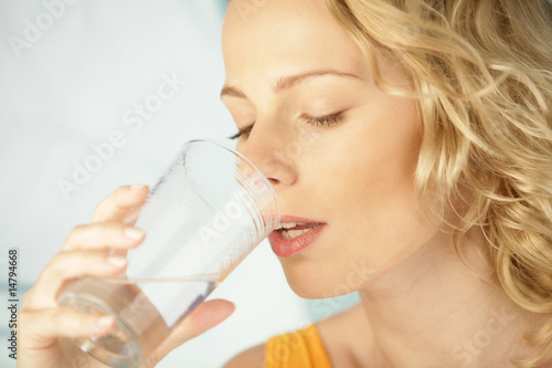 Young beauty blonde woman drinking mineral water