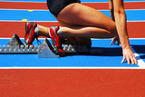 Woman in a starting block on an athletic field poster