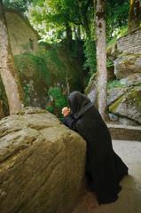 frommer Mönch betet vor Meditationsstein im Kloster