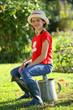petite fille assise sur un arrosoir dans le jardin