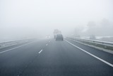 Fototapety Foggy gray road, cars driving into the fog