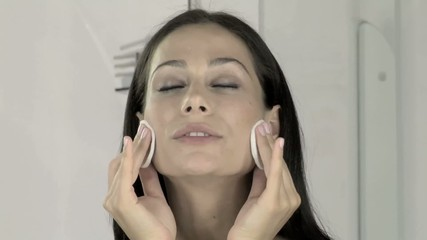 donna usa dischetti per pulizia del viso