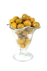 Green olives in a glass vase on a white background
