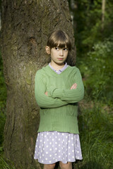 little cute serious girl standing at tree