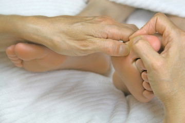 Close-up of reflexologist working on woman's big toe