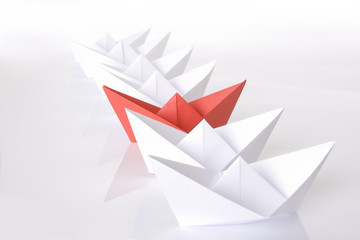 Red paper boat in the line