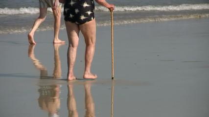 Señora coja andando por la playa