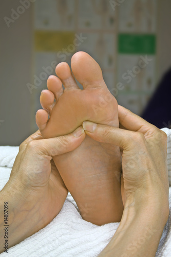 Reflexologist working the diaphragm area on woman's foot