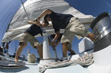 Sailors operating windlass on yacht, low angle view