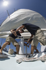 Sailors operating windlass on yacht, low angle view, wide angle lens