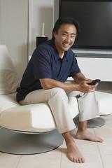 Man Sitting in Modern Living Room Holding Remote, portrait