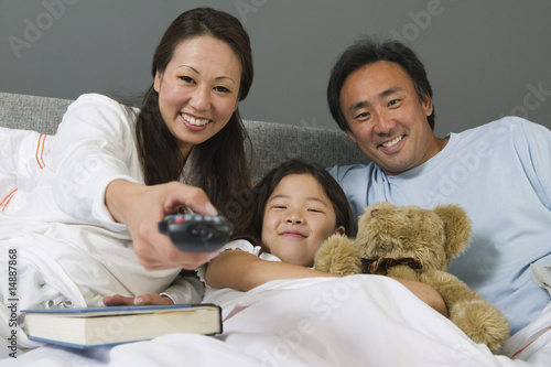 Family Watching TV Together in Bed, mother using remote control