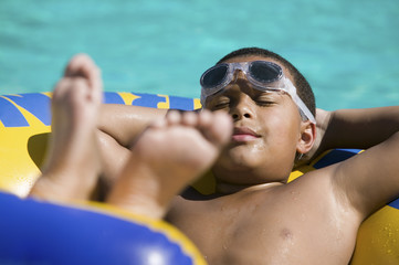 Boy 10-12 Relaxing on inflatable raft in swimming pool.