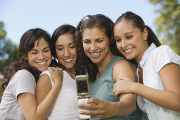 Woman using mobile phone, photographing self with three women.
