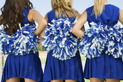 Cheerleaders holding pom-poms, rear view, mid section, close-up