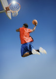 Basketball player shooting with ball, low angle view