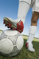 Soccer player 13-17 standing on ball, low section