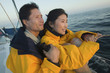 Couple wearing yellow anoraks on yacht